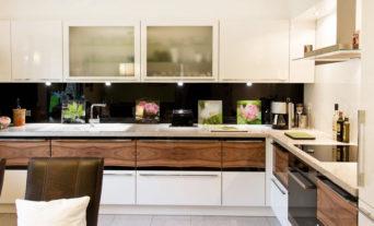 Küche in Hochglanz weiß mit Holzmaserung in Front und Naturstein-Arbeitsplatte
