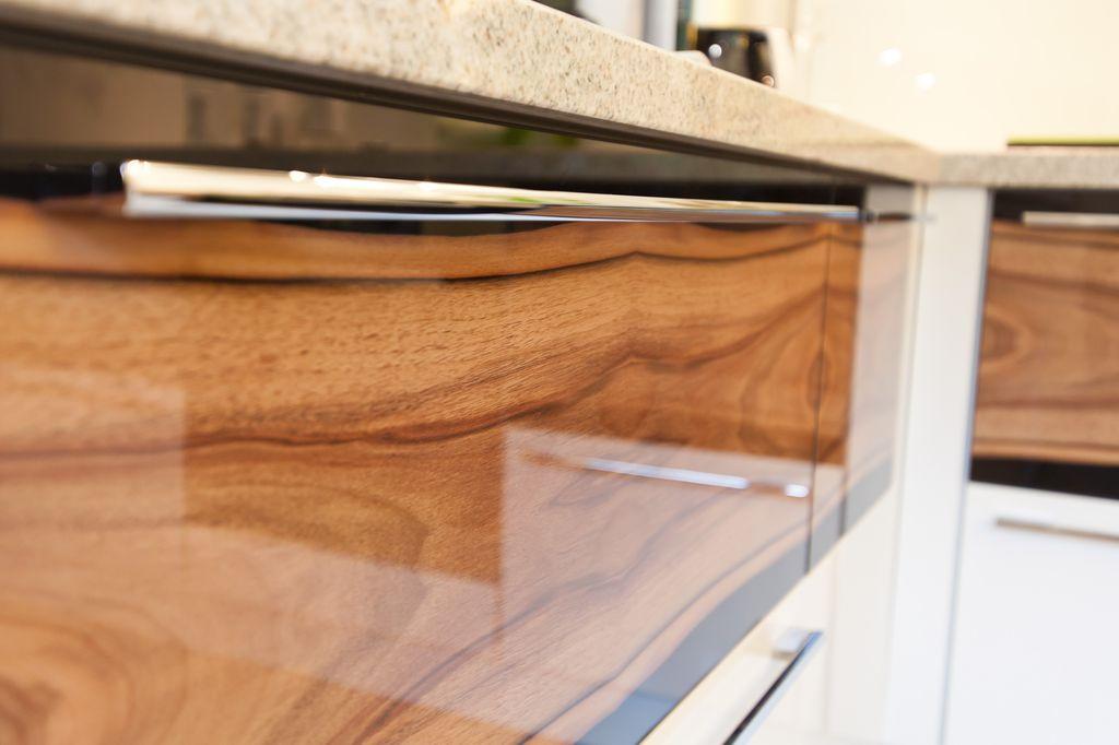 Küche in Hochglanz weiß mit Holzmaserung in Front und Naturstein ...