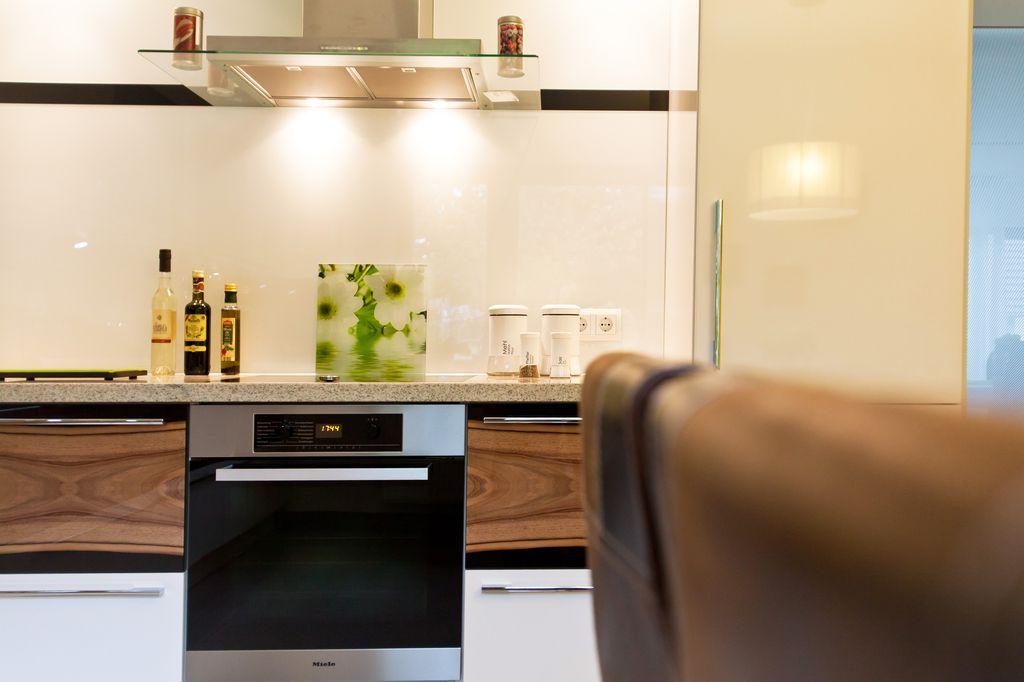 k che in hochglanz wei mit holzmaserung in front und naturstein arbeitsplatte k chenhaus. Black Bedroom Furniture Sets. Home Design Ideas