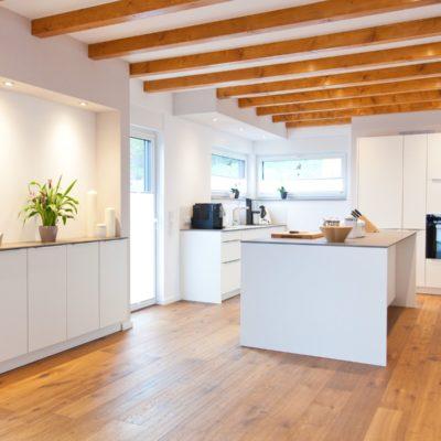 Weiße küche modern in szene gesetzt im landhausstil mit keramik arbeitsplatte und bora kochfeld küchenhaus thiemann overath vilkerath